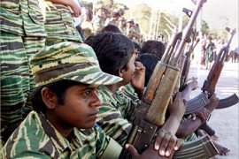 Female Liberation Tiger of Tamil Eelam (LTTE) cadres watch Tamil Women's Day celebrations in the rebel-held northern Sri Lanka town of Kilinochchi on October 10, 2002. The day marks the anniversary of the death of the first female cadre killed in combat during the Tiger's 19-year battle for a separate state in Sri Lanka's north and east. Picture taken October 10, 2002.   REUTERS/Anuruddha Lokuhapuarachchi    TO ACCOMPANY FEATURE SRILANKA-TIGERS-WOMEN