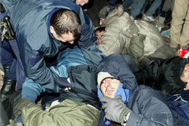 French riot policemen attempt to remove some of the refugees who had were sleeping on the streets of Calais