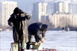 Russian fishermen prepare their lines for a day of fishing on the frozen Moskva river in Moscow, December 8, 2002. Early frosts hit Russia's capital with night temperatures plummeting to minus 25 degrees Celsius, which is 15 degrees lower then average winter temperatures.    REUTERS/Viktor Korotayev