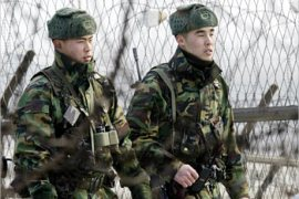 South Korean soldiers patrol inside the barbed-wire fence at Imjinkak, near the Demilitarized zone separating South and North Korea, in Paju about 50 km (31 miles) north of Seoul, January 10, 2003. North Korea withdrew from the global nuclear arms control treaty on Friday, escalating a crisis over its weapons ambitions just as two of its diplomats met Washingto's former U.N. ambassador to try to end the impasse.   REUTERS/Kim Kyung-Hoon