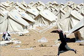 A Jordanian runs in front of a tent camp, managed by the Hashemite Charitable Organisation with the help of the United Nations High Commissioner for Refugees (UNHCR), in Rweished some 60 km (38 miles) from the Iraqi-Jordanian border, March 22, 2003. The tents are being erected for any Iraqis who might flee the country after the United States launched a war to disarm Iraq, but no Iraqis have yet arrived the camp.    REUTERS/Wolfgang Rattay