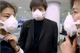 "Chinese travellers wear masks to ward off the deadly Severe Acute Respiratory Syndrome (SARS) at Beijing Capital Airport April 19, 2003. China said on Sunday it was cancelling the Labour Day ""Golden Week"" holidays to avoid the spread of SARS. The Health Ministry raised its count of SARS cases in China's capital almost 10-fold after they admitted there were 339 people infected with SARS and 402 suspected cases as of April 18. Eighteen people had died.  Picture taken April 19.    REUTERS/Wilson Chu"
