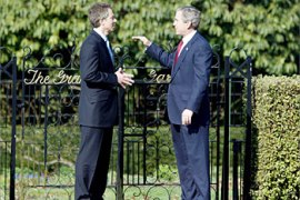 U.S. President George W. Bush (R) makes a point to Britain's Prime Minister Tony Blair in the grounds of Hillsborough Castle near Belfast after a bilateral meeting in Northern Ireland April 8, 2003. Looking beyond the war, President Bush and Blair are trying to bridge differences over how to rebuild and govern Iraq, while also seeking to boost peace talks in Northern Ireland.   REUTERS/Jason Reed REUTERS