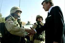 U.S. civil administrator to Iraq L. Paul Bremer (L) greets U.S. military police oficers at a police compound in Baghdad May 21 2003. The U.S. military police are now undertaking on a regular basis joint patrols of Baghdad with the Iraqi police force.     REUTERS/Kieran Doherty