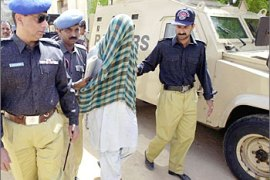 Pakistani policemen escort a suspect with his face covered, into a courtroom in Karachi, 09 May 2003.  The suspect was one of two arrested on May 02 when police intercepted a truck on a main highway and seized a large cache of explosives, including sulphur and other chemicals that could be used in making bombs. The court remanded suspects Muhammad Anwer and Habibullah to police custody till May 13.    AFP PHOTO/ Aamir QURESHI
