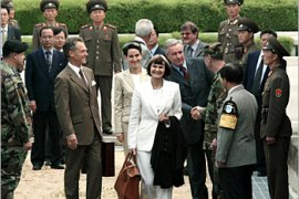 Swiss Foreign Minister Micheline Calmy-Rey (C) steps over the military demarcation line which seperates North Korea (rear) from South Korea at the Panmunjom truce village May 20, 2003. Micheline Calmy-Rey came to Seoul on Tuesday through the Panmunjom truce village after visiting Pyongyang since May 17. Land crossings through the demilitarized zone by foreign dignitaries are very rare.   REUTERS/Kim Kyung-Hoon