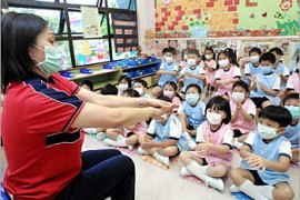 A kindergarten teacher illustrates to students how to wash their hands as the first day of kindergarten classes resumed, 19 May 2003, at the Hong Kong Soka Kindergarten, following their closure during the Severe Acute Respiratory Syndrome (SARS) crisis.  Hong Kong health authorities said 18 May the transmission of the deadly SARS virus in the community was under control with just three new infections, bolstering the case for the lifting of a six-week old World Health Organisation (WHO) travel warning on the territory.   AFP PHOTO/Thomas CHENG