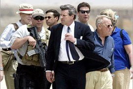 New U.S. civilian administrator to Iraq L. Paul Bremer (C) and retired General Jay Garner (R) are surrounded by security after landing at Baghdad's airport May 12, 2003. Bremer who replaces Garner will take over reconstruction and political rehabilitation after the war that ousted Saddam Hussein.    REUTERS/Kevin Coombs