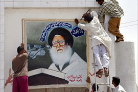 R_Iraqi men in Basra paste a picture of a revered Shi'ite cleric over a defaced portrait of Saddam Hussein, May 26, 2003. Following the downfall of Saddam, Shi'ite leaders long suppressed by the former regime have become the most powerful political figures in southern Iraq.  REUTERS/Andrea Comas REUTERS