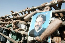 F_A man holds up a poster of Iranian President Mohammad Khatami as he waits behind a fence with others for Khatami to appear at a rally in Shahriar, 35km southwest of Tehran, 25 June 2003. Iran's reformist-controlled parliament set up a five-member committee to meet students detained during the recent wave of unrest across the country, and have called on families to provide the names of any missing students, press reports said. The move comes amid concerns over how many students were detained during the June 10-20 unrest, which saw a small protest at Tehran University over government education policy snowball into 10 days of countrywide anti-regime demonstrations and clashes.     AFP PHOTO/Atta KENARE