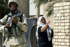 An Iraqi woman gestures as a US soldier carries out a foot patrol in Baghdad 15 July 2003. The killing of a soldier and a grenade blast outside the coalition's Baghdad headquarters yesterday raised fears as the anniversary dates approached for toppled leader Saddam Hussein, while US troops faced an indefinite stay in Iraq