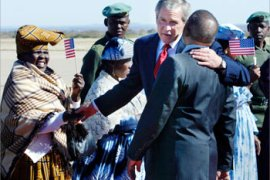 U.S. President George W. Bush, puts his arm around Botswana President Festus Mogae as he greets a receiving line upon arrival at Sir Seretse Khama International Airport in Gaborone, Botswana, July 10, 2003. Bush discussed trade, the war on terror and the AIDS epidemic with Mogae.   REUTERS