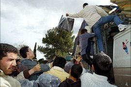 Moroccans rush on a truck carrying mattressed and blankets sent by humanitarian organisations at the airport of El Houceima 26 February 2004