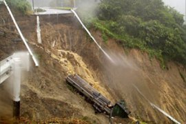 AFP – A large truck lies on the sloap after the landslide swept the road