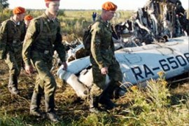 Russian Emergencies ministry servicemen inspect the wreckage of a Russian Tupolev Tu-134 plane near Tula, some 150 km from Moscow, August 25, 2004. Two Russian passenger planes carrying more than 80 people crashed almost simultaneously on Tuesday, and security officials said they were investigating a possible terrorist attack.  REUTERS/Sergei Karpukhin