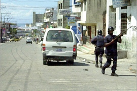 AFP – Haitian police patrol a street 11 October 2004 in Port-au-Prince following violent protests by supporters of ousted