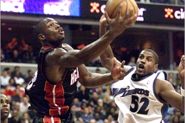 REUTERS – Miami Heat's Dwyane Wade (L) drives around Washington Wizards' Samaki Walker (52) for a layup attempt in the fourth