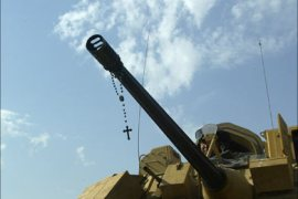 F_A rosary hangs off the barrel of a machinegun mounted on a Bradley belonging to the 1st Cavalry Regiment 5th Battalion