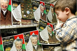 REUTERS – A Palestinian boy looks at posters of Palestinian President Yasser Arafat in a shop in the West Bank city of Nablus