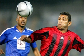 REUTERS  /Al-Rayyan's Sonny Anderson of Brazil (R) fights for the ball with Al-Khor's Mohamad Juma of Bahrain during their Crown Prince Cup soccer match in Doha May 3, 2005.