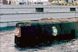 r – The conning-tower of the Kursk nuclear submarine surfaces in a dock of Roslyakovo port near Murmansk in this October 23, 2001 file photo