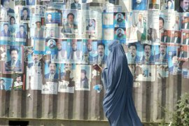 A burqa clad Afghan woman walks past a wall covered in posters featuring images of parliamentary election candidates in Kabul, 30 August 2005.