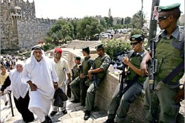 . AFP-  Israeli border police officers stand guard as a muslim man walks next to him at Damascus Gate in Jerusalem Old City 05 August 2005 after the friday prayer. Security forces