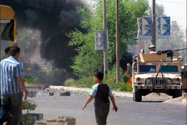 afp/Iraqi civilians watch as a U.S. military Humvee burns following a car bomb attack in Baghdad September 5, 2005.