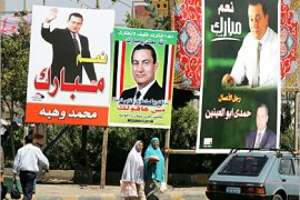 AFP –  Egyptian civilians walk past electoral posters and billboards promoting Egyptian candidate and current President Hosni Mubarak, 06 September 2005 in Cairo. Mubarak, who has
