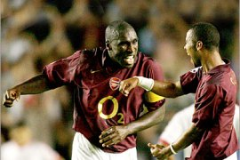 REUTERS/  Arsenal's Sol Campbell (L) and Ashley Cole (R) celebrate Dennis Bergkamp's (unseen) winning goal during their Champions League Group B soccer match at Highbury