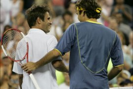 afp – Number one seeded Roger Federer (L) of Switzerland shakes hands with Fabrice Santoro of France as they walk off the court after their match at the US Open 2 September