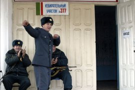 A Chechen policeman dances in front of a polling station on election day in Grozny November 27, 2005. Chechens were voting on Sunday for a regional assembly that is unlikely to appease anti-Moscow rebels but is expected to cement the power of a local pro-Russian strongman.