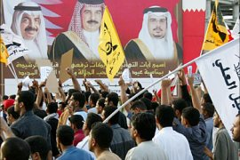 r_Demonstrators shouting anti-government slogans walk past a billboard bearing pictures of the King of Bahrain
