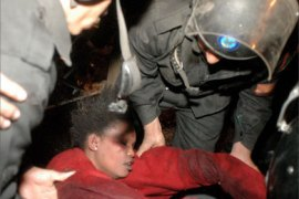 An unconscious Sudanese woman is being lifted by Egyptian riot police in a Cairo public square December 30, 2005. A young Sudanese girl of about four died when Egyptian police fought on Friday with thousands of Sudanese demanding to be allowed to start new lives abroad