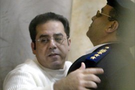 An Egyptian policeman pushes back Ayman Nour, leader of the opposition Ghad party, after his conviction at a court in Cairo 24 December 2005. Hosni Mubarak's runner-up in Egypt's presidential election