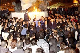 epa00599883 Lebanese Daniel Sbiro looks at the flame he lit to start the protest in 'Camp Freedom' on the Martyrs' Square, in Beirut, Monday 19 December 2005. Anti-Syrian