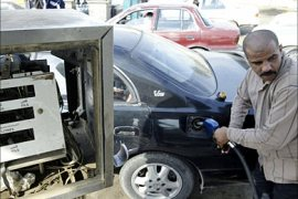f_An Iraqi man fuels his vehicle at a gas station in central Baghdad, 20 December 2005. Three
