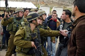 f_Israeli soldiers arrest a Palestinian at the Beit Furik checkpoint near the West Bank city of Nablus