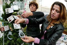 f_Georgette Bashour (R), sister of a missing Lebanese since 1990, decorates a Christmas tree with pictures