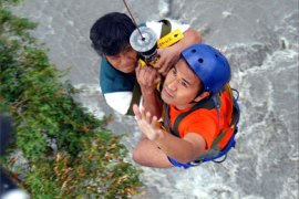 A rescuer (R) helps a man trapped in flood waters into a helicopter at Calapan, 18 December 2005.  Widespread flooding in the central Philippines has brought the death toll to six with nearly 13,000 other residents displaced, rescuers said 19 December
