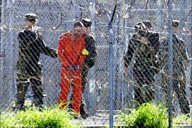 f_Picture taken 17 January, 2002 shows a detainee (2nd L) wearing an orange jump suit