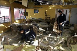 Palestinian men inspect the damaged drinking hall of a club for the United Nations after it was blown up in Gaza City early 01 January 2006. Armed and masked Palestinian militants took control of the United Nations club in Gaza City today before detonating explosives inside the building,