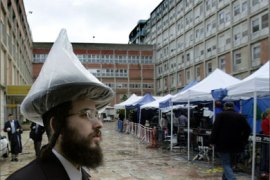 An ultra-Orthodox Jew stands 08 January 2005 at the courtyard of Hadassa Hospital in Jerusalem next to tents set up for the media covering Israeli Prime Minister Ariel Sharon's battle for life.