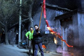 A man burns a stick of over 1,000 firecrackers during loud celebrations moments after midnight in an old Beijing neighborhood near the ancient Bell Tower, early 29 January 2006