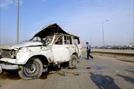 An Iraqi policeman secures that site where a roadside bomb exploded in central Baghdad destroying a civilian car and wounding two Iraqis, 01 February 2006. Three Iraqis were killed and 61 were wounded by a suicide bomber wearing an explosive belt in a southern Baghdad today