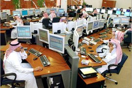 -AFP  – Saudi employees work the phones inside the traders room at the Saudi Investment Bank in Riyadh 19 March 2006. The Saudi stock market, the largest in the Arab world, fluctuated