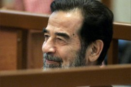 Former Iraqi President Saddam Hussein smiles as he attends his trial at the Hevaily Fortified Green Zone in Baghdad, 05 June 2006