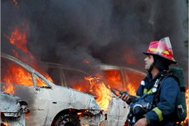 epa00794229 An Israeli firefighter extinguish burning cars caused by a Hezbollah rocket , in the northern Israeli city of Haifa, Sunday, 13 August 2006. Hours before the UN brokered ceasefire between Israel and Hezbollah was to go into effect, more than 250 rockets were fired by the militant
