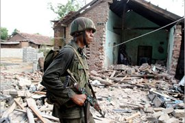 REUTERS /A Sri Lankan government soldier walks past a bombed house in the northeastern town of Muttur August 5, 2006.  Days of fighting with Tamil Tiger rebels rendered the road