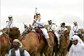 epa00871255 Torch bearers riding camels at the Camel race track in Al Jumailiyah, Qatar during the torch relay on Sunday 26 November 2006, on Day 50 of the 15th Asian Games Doha 2006 torch relay event.The relay is the longest in the history of the Games, travelling 50,000 km (31,069 miles) to 15 countries and regions in 55 days returning to Doha for the opening ceremony of the 15th Asian Games.  EPA/RICK STEVENS / POOL  EDITORIAL USE ONLY